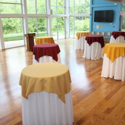 High top tables with maroon and gold tablecloths